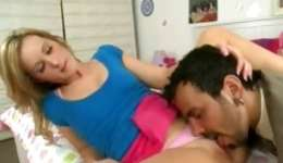 Sexy looking blonde lying on a bed and engulfing a tasty erect boner